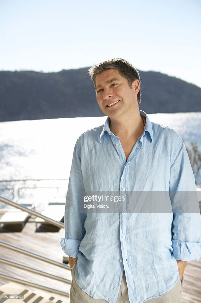Mature Man in a Summer Shirt Stands on Steps by the Water : Stock Photo