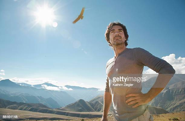 mature man in andean scenery, condors flying - hand on hip stock pictures, royalty-free photos & images