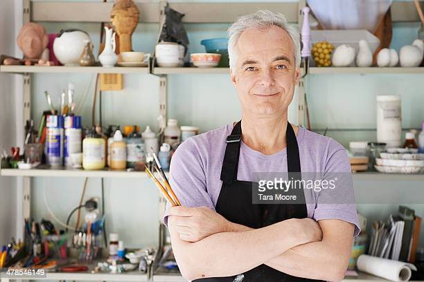 mature man in artist's studio - artist stock pictures, royalty-free photos & images