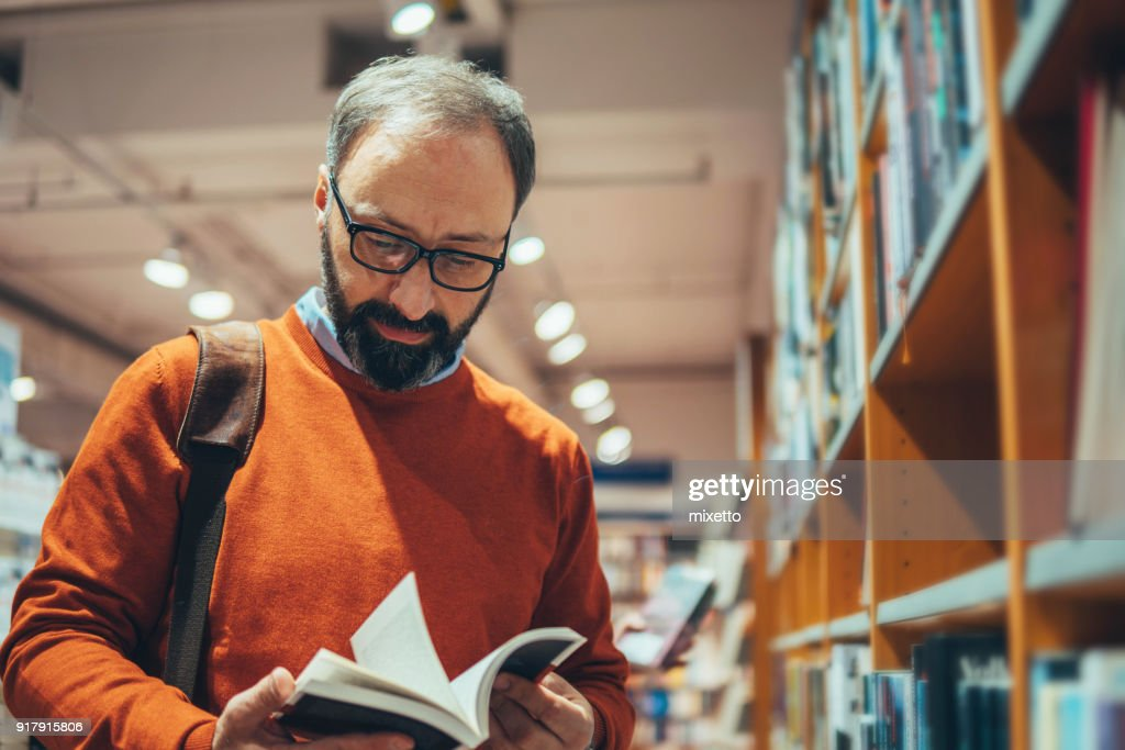Mature man in bookstore : Stock Photo