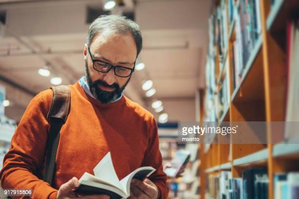 mature man in bookstore - book shop stock pictures, royalty-free photos & images