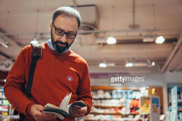 mature man in bookstore - book store stock photos and pictures