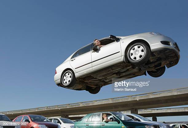 Mature man in car in air above people in traffic jam
