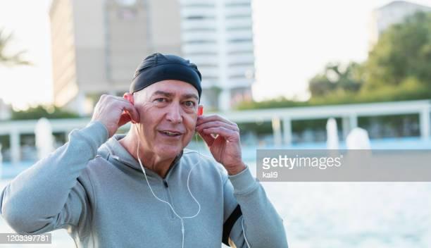 イヤホンを着て街の成熟した男 - スカルキャップ ストックフォトと画像