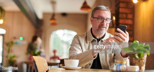 mature man in coffee shop with smartphone - the internet stock pictures, royalty-free photos & images
