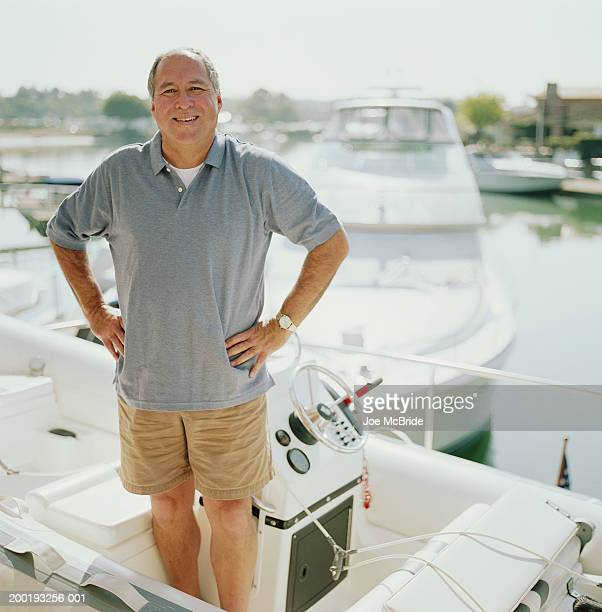Mature man in dinghy of yacht docked in harbor, portrait