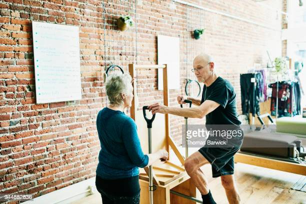 Mature man in discussion with mature female pilates instructor before exercising on high-low chair in fitness studio
