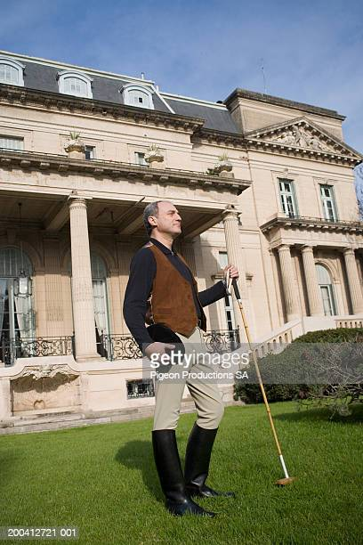 mature man in front of house with polo stick - 乗馬ズボン ストックフォトと画像