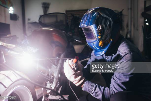 Mature man in garage, working on motorcycle, using welding equipment