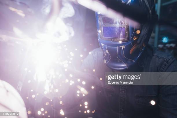 Mature man in garage, working on motorcycle, using welding equipment