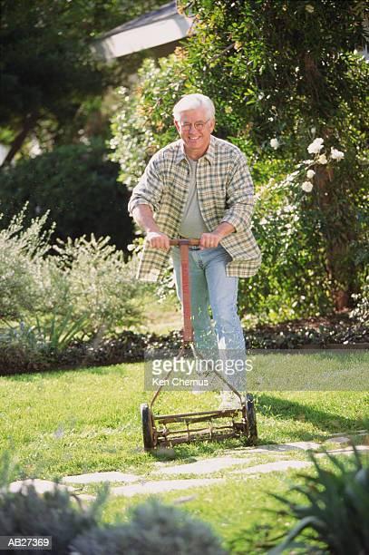 Mature man in garden cutting grass