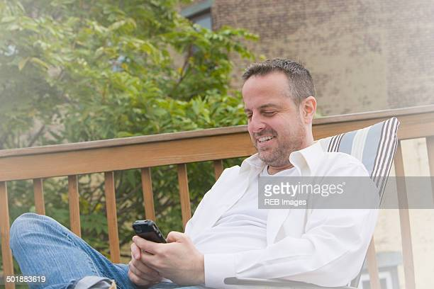 Mature man in garden deck chair texting on smartphone