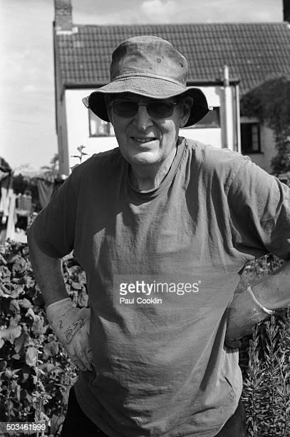 Mature man in garden wearing gardening gloves and sun hat Beccles Suffolk