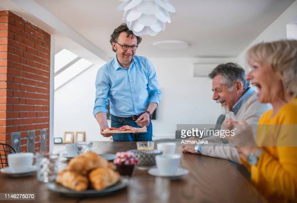mature man in glasses bringing charcuterie to his guests at the brunch table - charcuterie board stock pictures, royalty-free photos & images