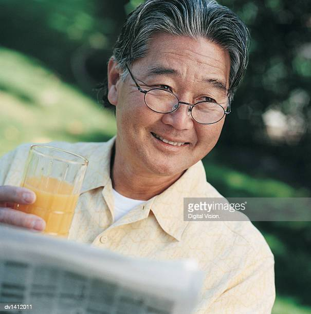 mature man in his back yard holding a glass of orange juice and a newspaper - 男性一人 ストックフォトと画像