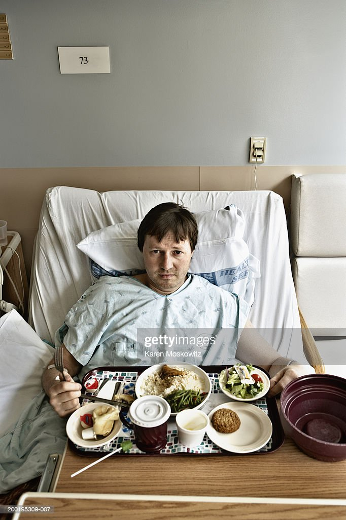 Mature man in hospital bed with tray of food, elevated view, portrait : Stock-Foto