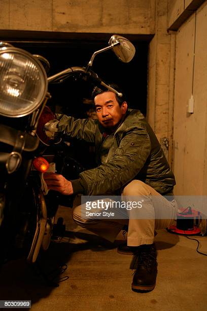 Mature man in jacket cleaning a motorcycle