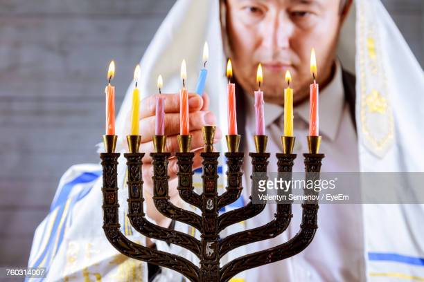 Mature Man In Jewish Prayer Shawl Burning Candles On Hanukkah Menorah