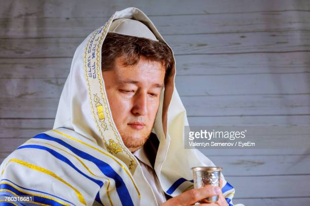 mature man in jewish prayer shawl holding kiddush cup - jewish prayer shawl ストックフォトと画像