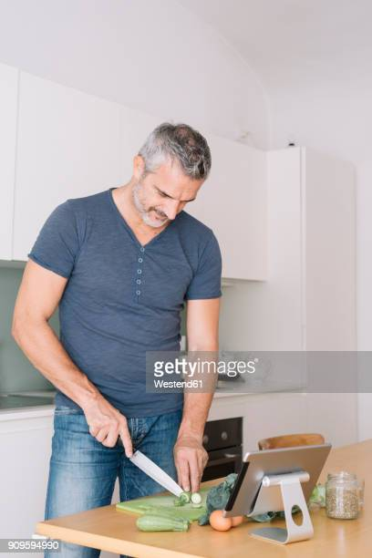 Mature man in kitchen cutting vegetables and looking at tablet