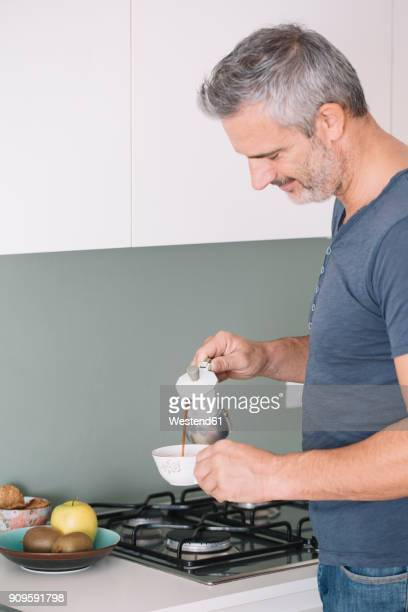 Mature man in kitchen pouring a cup of coffee