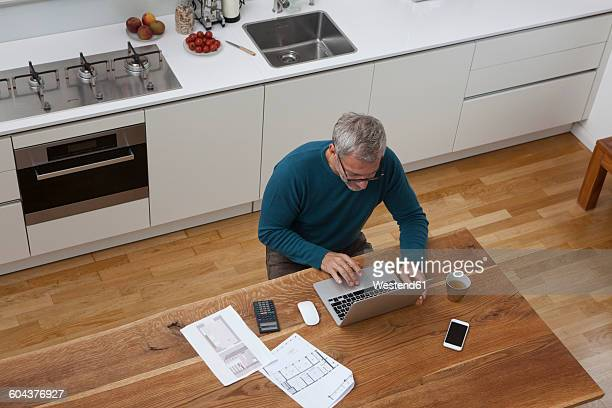 Mature man in kitchen with construction plan using laptop