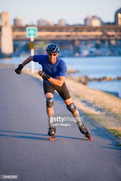 mature man in line skating by sea - caneleira roupa desportiva de proteção imagens e fotografias de stock