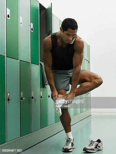 Mature man in locker room using mobile phone and putting on sock