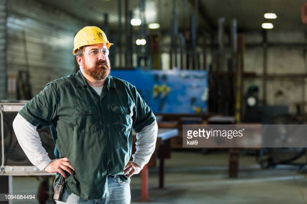 mature man in metal fabrication plant - hand on hip stock pictures, royalty-free photos & images