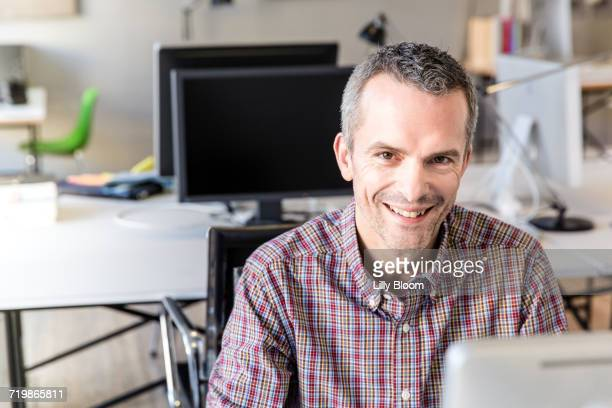 Mature man in office looking at camera smiling