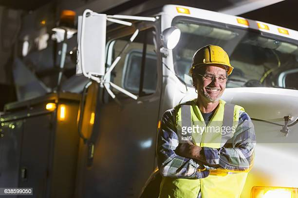 Mature man in safety vest, hardhat with truck