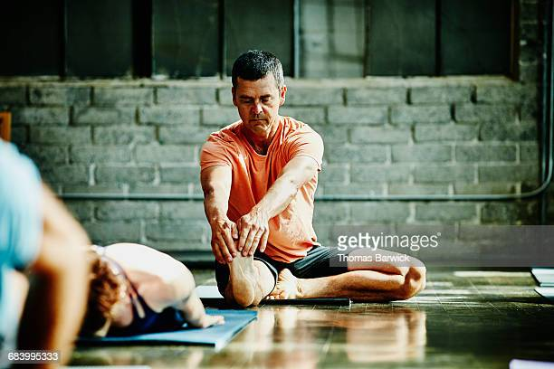 Mature man in seated stretch during yoga class