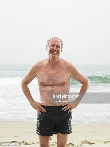 mature man in shorts standing on beach, hands on hips - einzelner senior stock-fotos und bilder