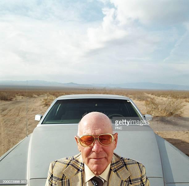 mature man in suit leaning against the hood of car, elevated view - lunettes de soleil teintées photos et images de collection