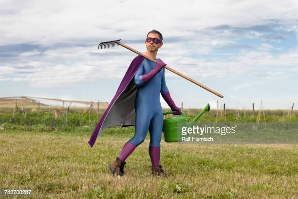 Mature man in superhero costume holding rake and watering can while walking on field against sky