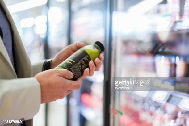 mature man in supermarket choosing smoothie from cooling shelf - koude dranken stockfoto's en -beelden