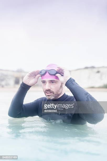 Mature man in the sea, wearing wetsuit, ready for a swim