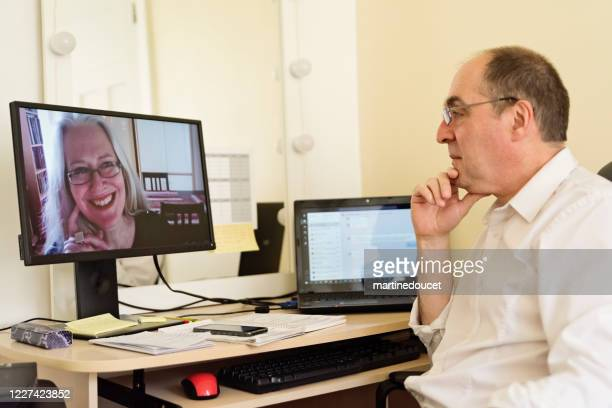 "mature man in video conference in temporary home office. - ""martine doucet"" or martinedoucet stock pictures, royalty-free photos & images"