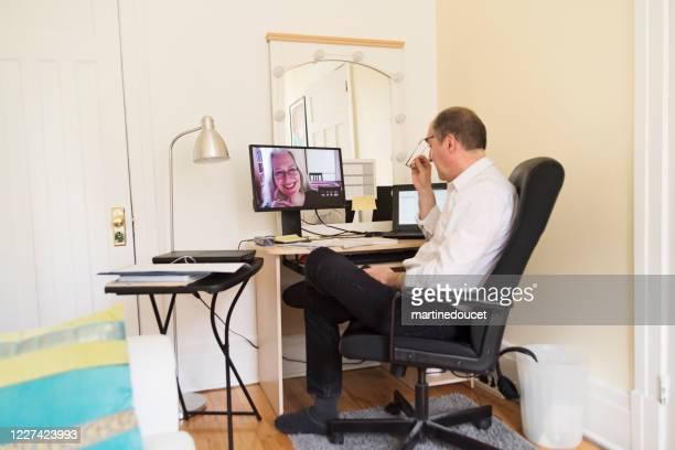 一時的なホームオフィスでのビデオ会議で成熟した男。 - 臨時 ストックフォトと画像