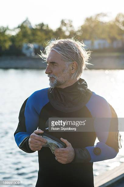 Mature man in wetsuit holding diving mask