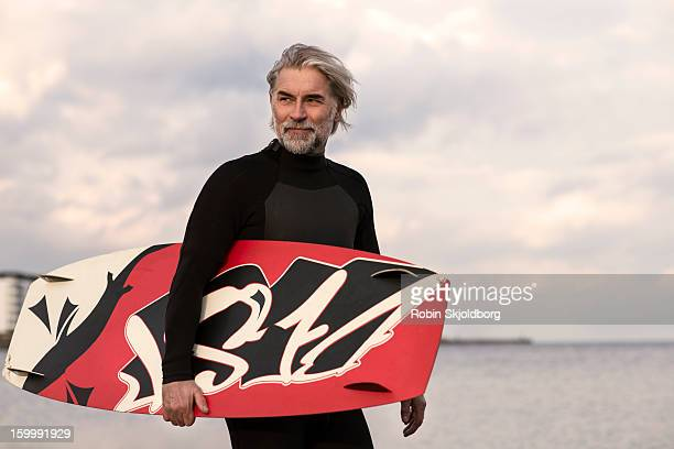 Mature man in wetsuit walking with kitesurf board