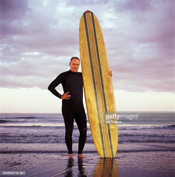 Mature man in wetsuit with surfboard at beach, portrait