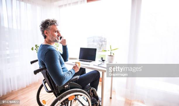 mature man in wheelchair with smartphone in home office. - wheelchair stock pictures, royalty-free photos & images