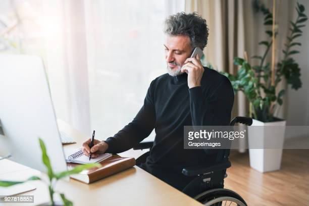 mature man in wheelchair with smartphone in home office. - human body part stock pictures, royalty-free photos & images