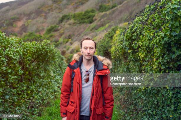 mature man in winter coat on a coastal footpath - one man only stock pictures, royalty-free photos & images