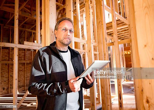Mature man inspecting construction site with tablet