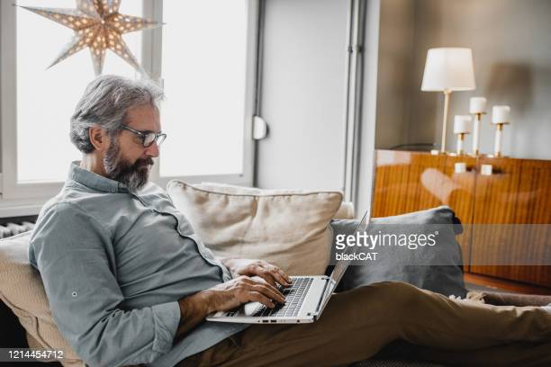 mature man is working from home - surfing the net stock pictures, royalty-free photos & images