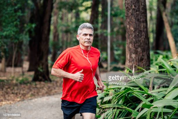 mature man jogging in woods with earphones - top garment stock pictures, royalty-free photos & images