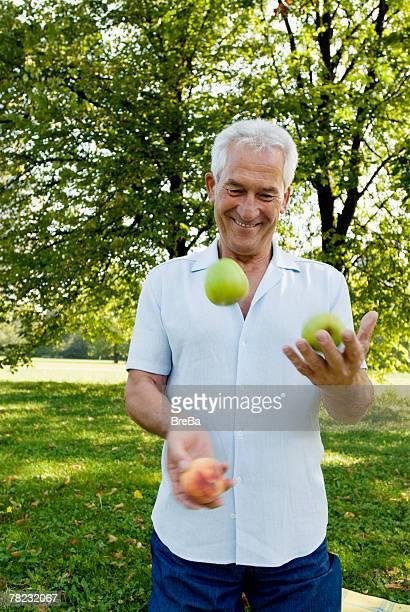 mature man juggling in park