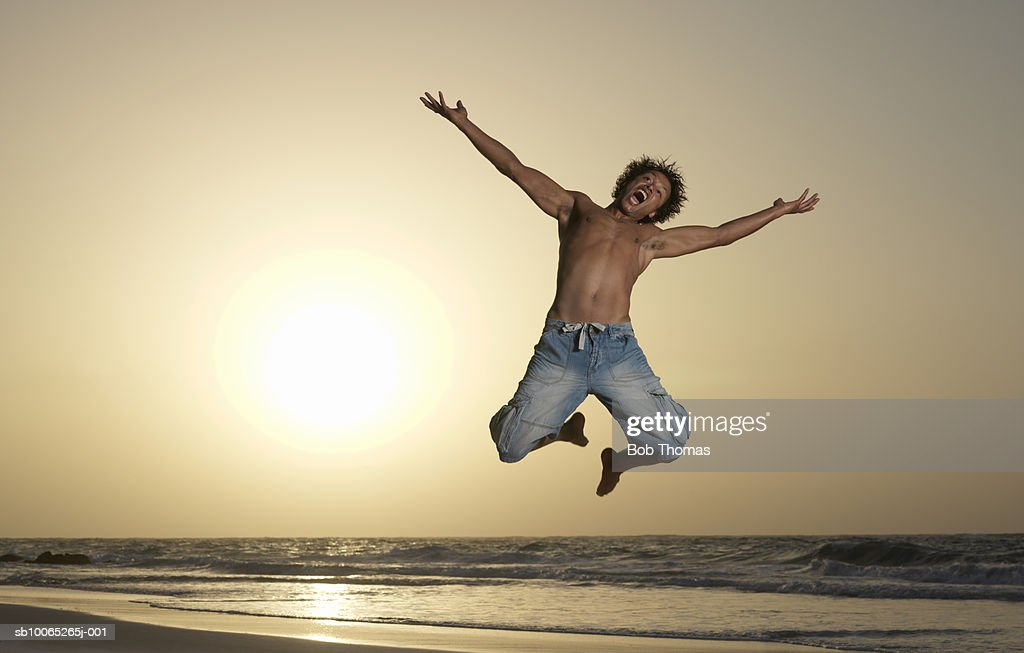Mature man jumping on beach, arms outstretched : Foto stock
